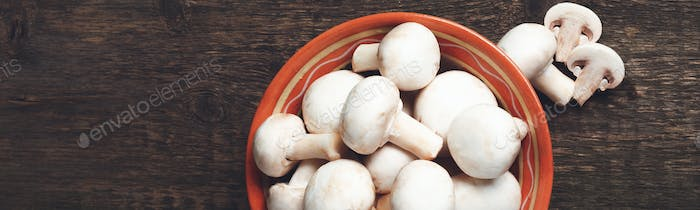 Banner of Fresh white mushrooms champignon in brown bowl