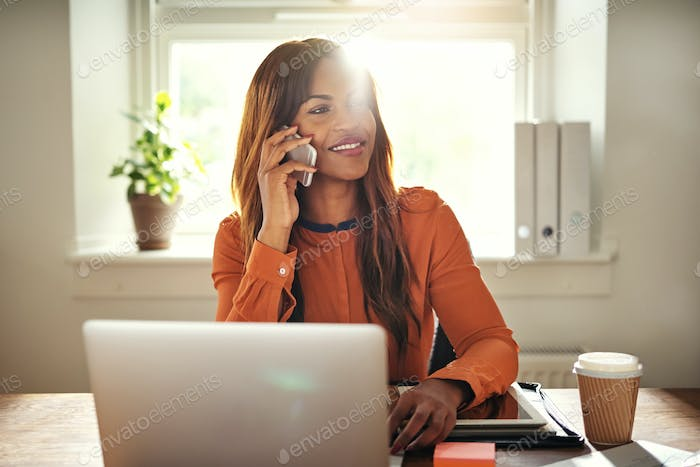 Young entrepreneur talking on a cellphone while working from home