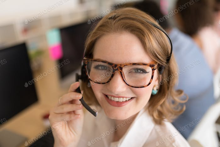 Portrait of happy young Caucasian female executive in headset smiling in modern office