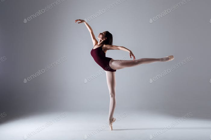 Young slim ballerina is dancing in a white stuidio with contrast light