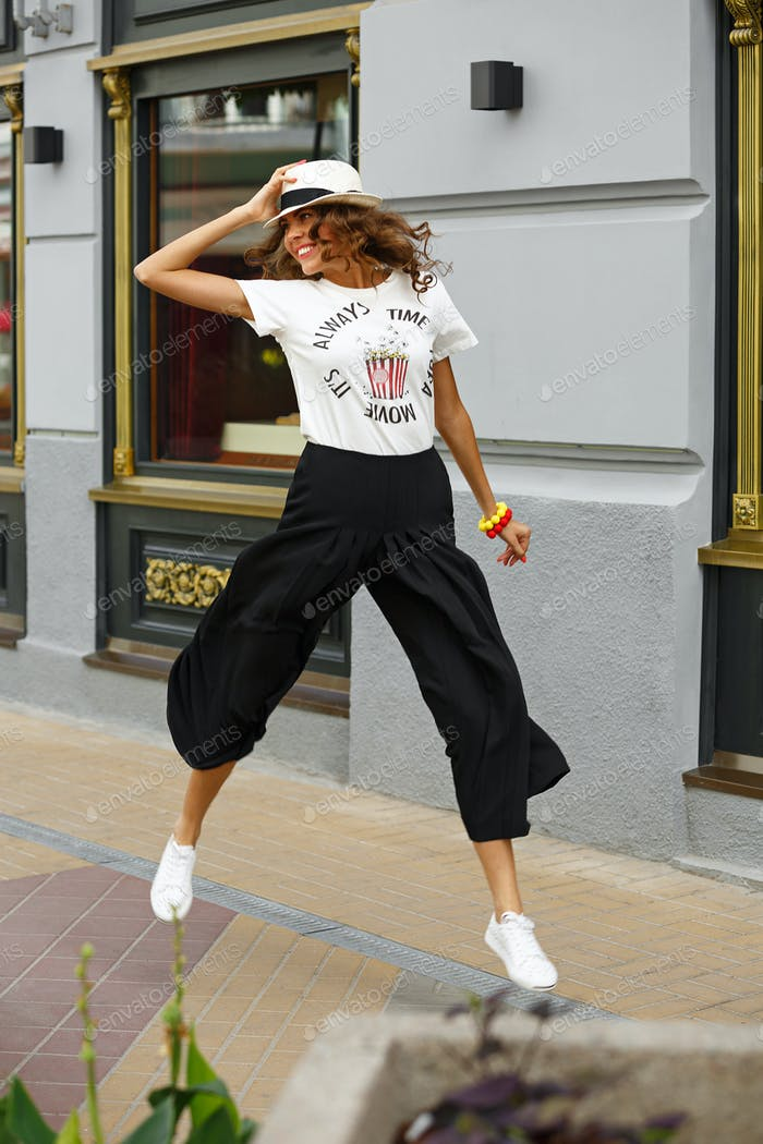 Stylish young girl dressed in a white t-shirt, black wide trousers and white sneakers is jumping in