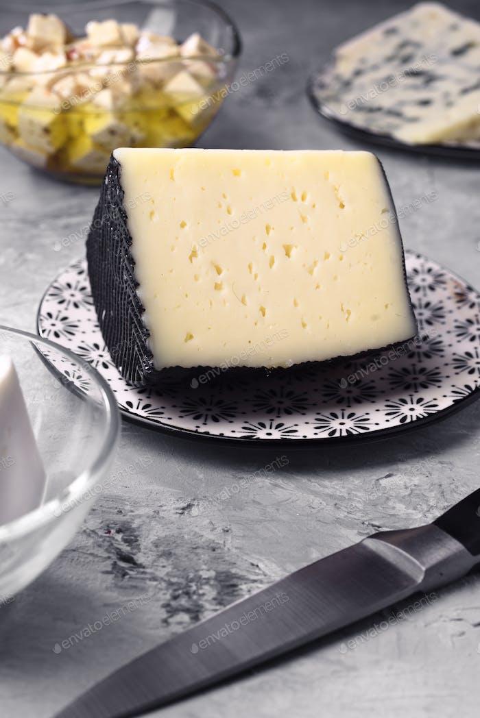 Stück spanischer Schafskäse und andere Käsesorten auf grauem marmoriertem Hintergrund