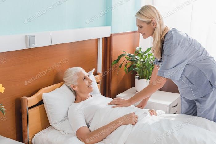 Krankenschwester und ältere Frau lächelnd einander in Pflegeheim