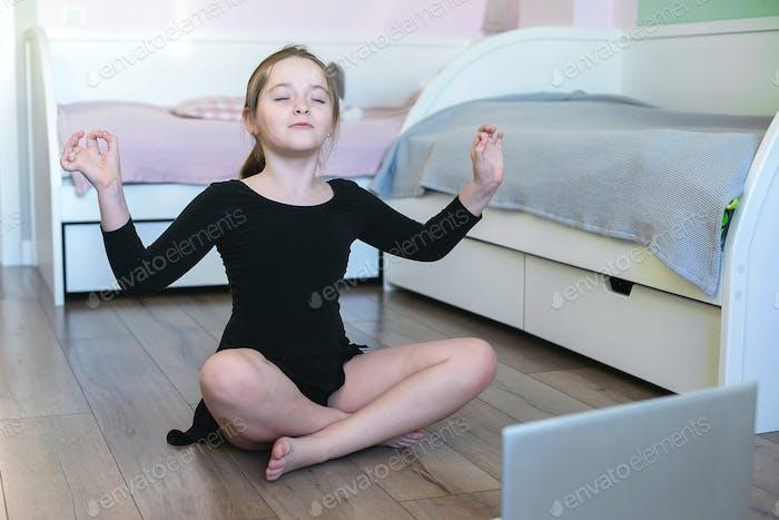 Schoolgirl watching online video and doing sports exercises yoga, gymnastics, choreography.