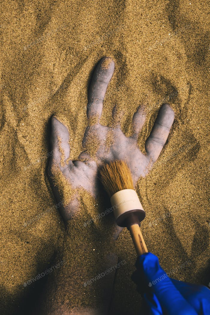 Forensic expert discovering dead body buried in desert sand