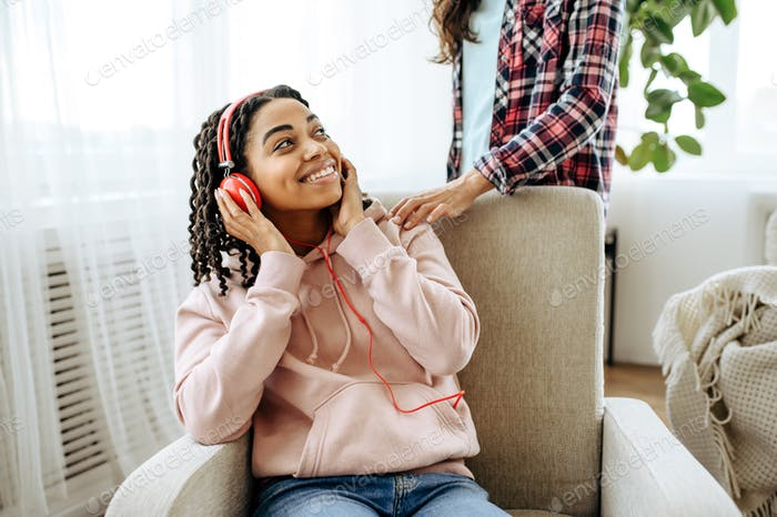 Two women jokes and listening to music