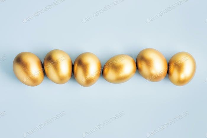 Goldene Eier auf blauem Pastell Hintergrund