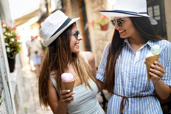 Two young female friends having fun and eating ice cream