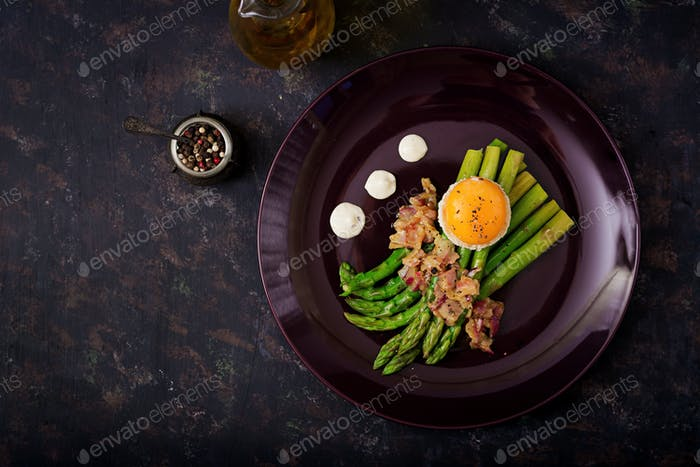 Young shoots of asparagus with ham and chicken egg yolk on toast