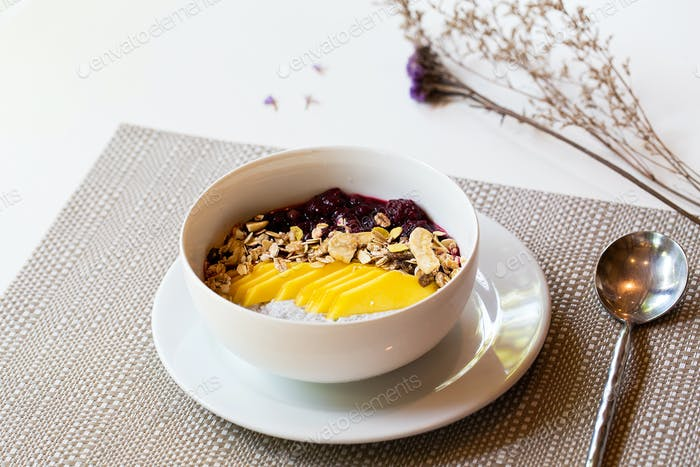 Breakfast berry smoothie bowl topped with blueberry,almond, banana and chia seeds