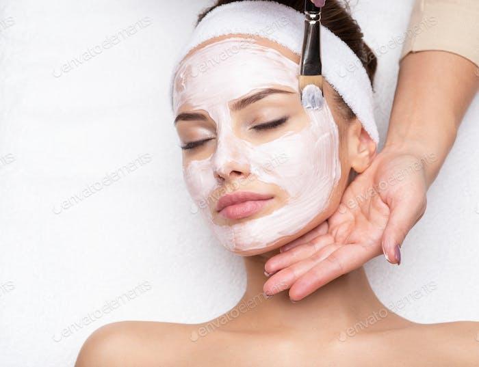 Mujer que recibe máscara facial en el salón de belleza