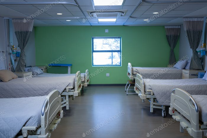 Front view of two rows of empty hospital bed in a hospital