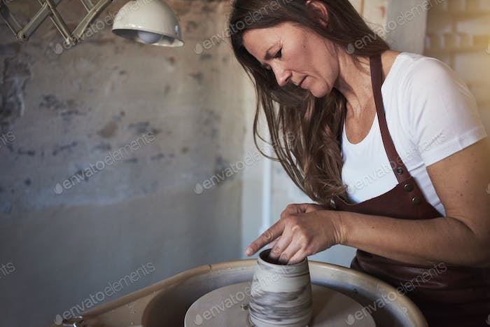 Female artisan creatively sculpting clay in her pottery studio