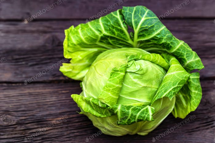 Green fresh cabbage head on wooden surface