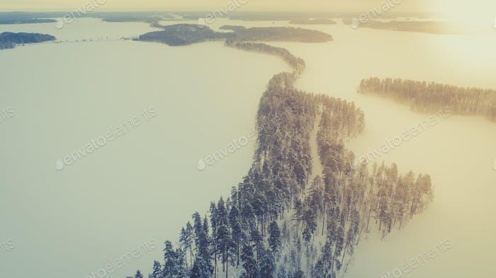 Воздушный вид на озеро и лес в холодный зимний день восхода солнца