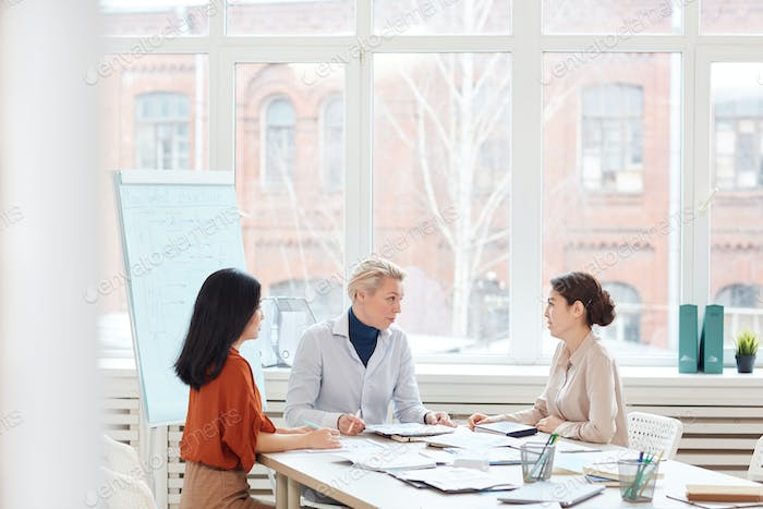 Women Discussing Work Project in Modern Office