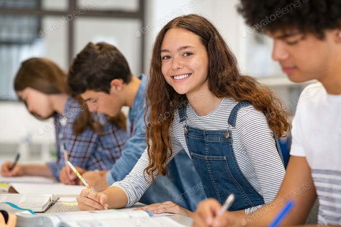 Portrait of happy high school girl studying in class