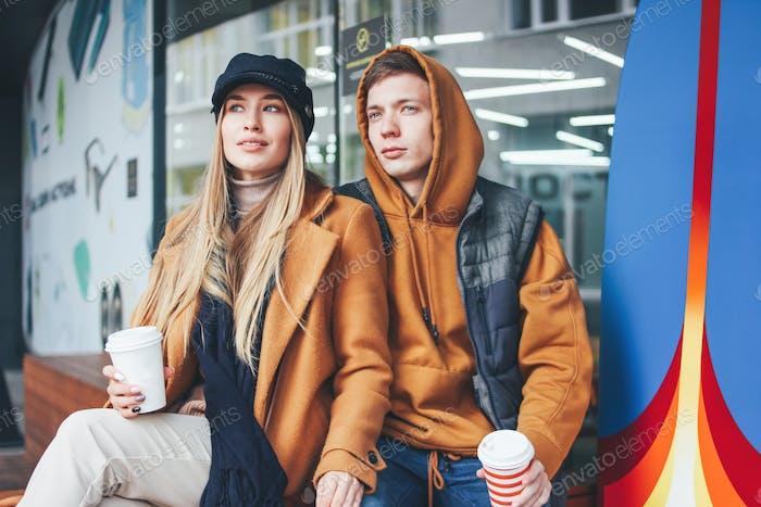 Glückliche junge Paar Freunde im lässigen Stil zu Fuß auf der Stadtstraße in der kalten Jahreszeit gekleidet