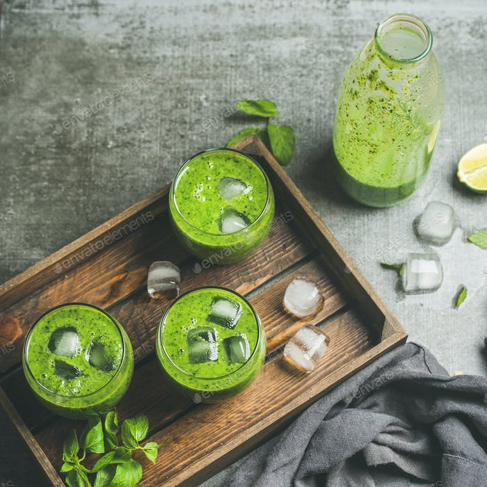 Fresh smoothie with ice cubes, mint, lime over grey background