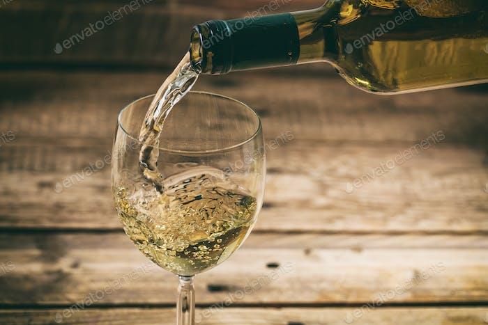 Weißwein in einem Glas auf Holzhintergrund gießen
