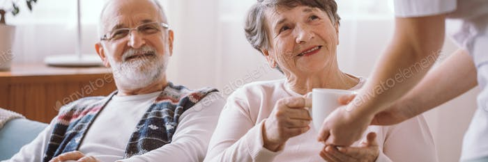 Happy grandmother taking a cup of tea from her caregiver in the nursing home