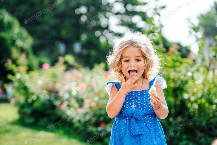 маленькая девочка ест мороженое