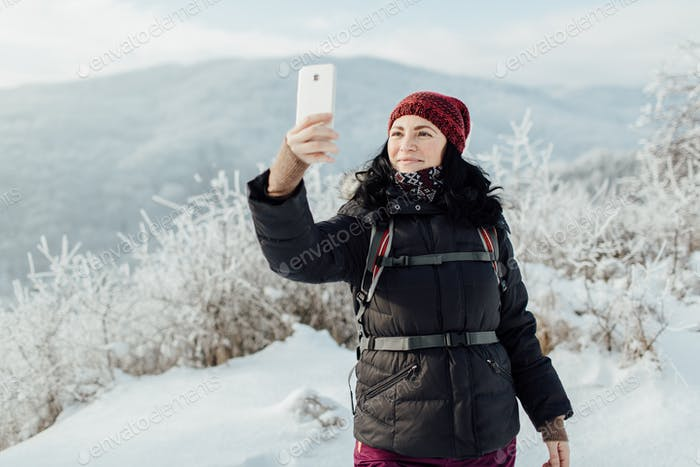 Smiling woman dressed warm taking a selfie in a snowy country