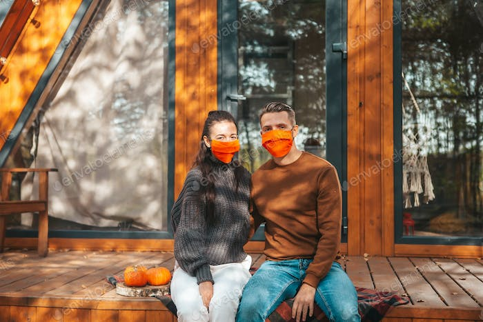 Family of two in masks on the terrace in autumn