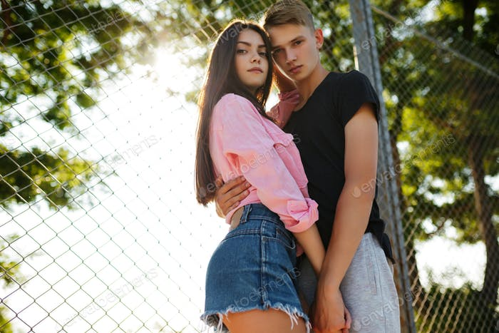 Young beautiful couple standing and embracing one another while thoughtfully looking in camera