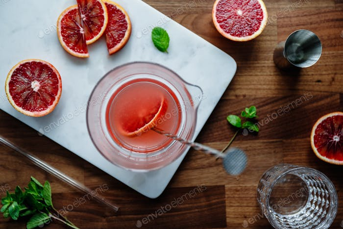 Mixing of refreshing cold summer cocktail with blood orange in a glass pitcher on a marble tray