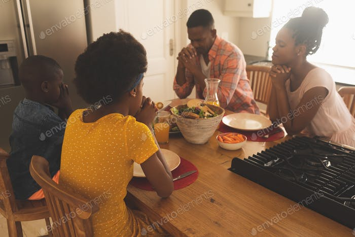 Family with hand clasped and eyes closed praying together at dining table