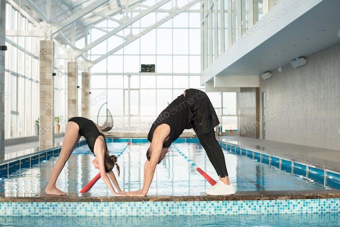 Trainer zeigt Übung zu kleinen Schwimmer