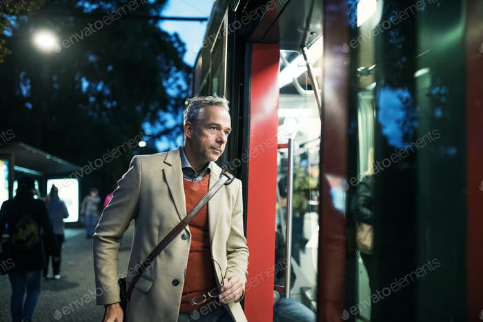 Mature businessman getting on a tram in the evening.