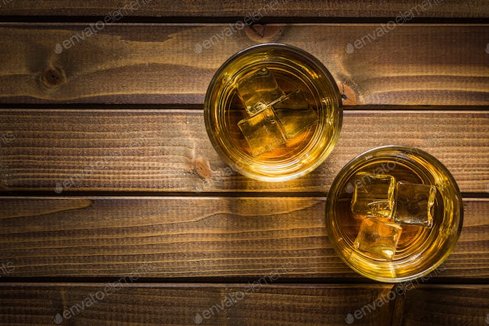 Glass of alcoholic drink with ice cubes on wooden table.