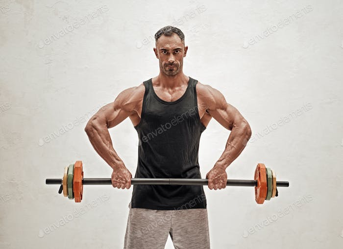Buffed sportsman posing in a bright studio with a barbell