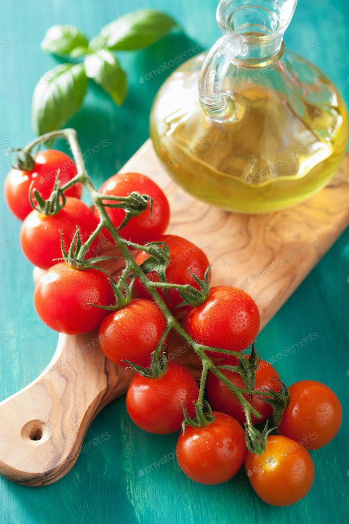 cherry tomatoes and olive oil over turquoise background
