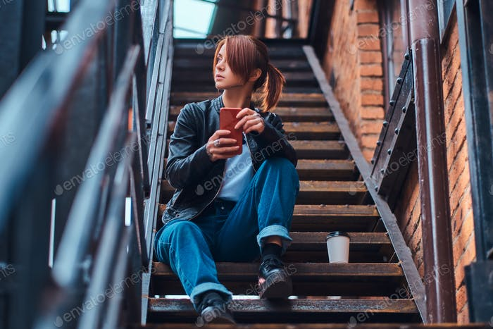 Redhead girl wearing trendy clothes sitting on stairs outside the cafe and holding a smartphone.