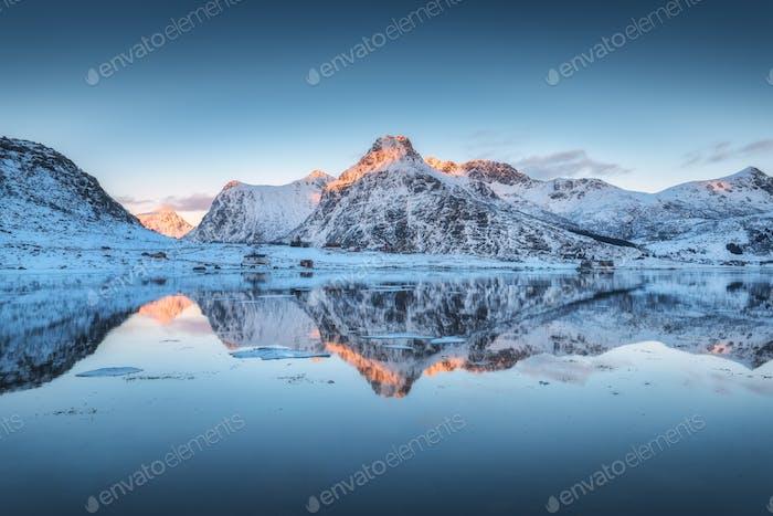 Fjord mit Reflexion im Wasser, verschneite Berge bei Sonnenuntergang