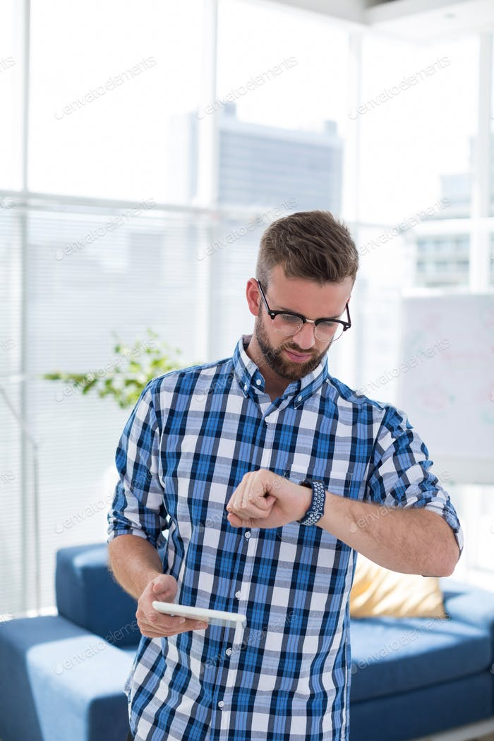 Male executive checking time on smartwatch