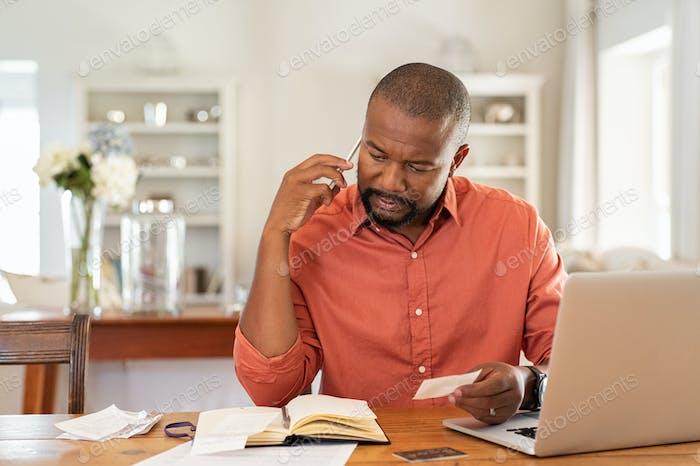 Besorgter Mann mit Rechnungen rufen Sie die Bank