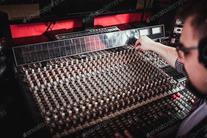 Recording studio mixing desk, music producer using soundboard