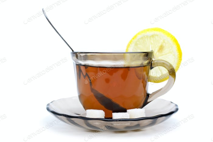 Teacup with black tea, teaspoon, dish, lemon slice and some sugar pieces