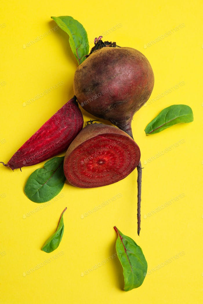 Ripe red beet with leaves on yellow background