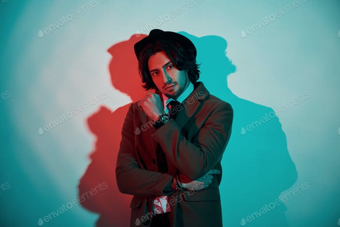 Portrait of young stylish man in hat, suit and tie that stands in neon lights in the studio