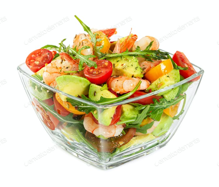 Salad with avocado, shrimp, fresh cherry tomatoes and arugula in glass bowl isolated on white