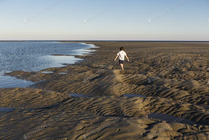 Ein sechsjähriger Junge untersucht sandige Landschaft