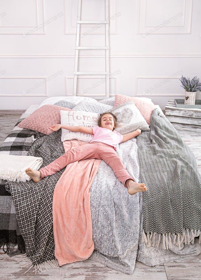 Милая маленькая девочка играет на кровати.