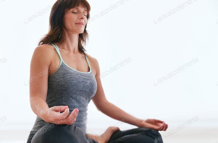 Woman practicing Padmasana at gym