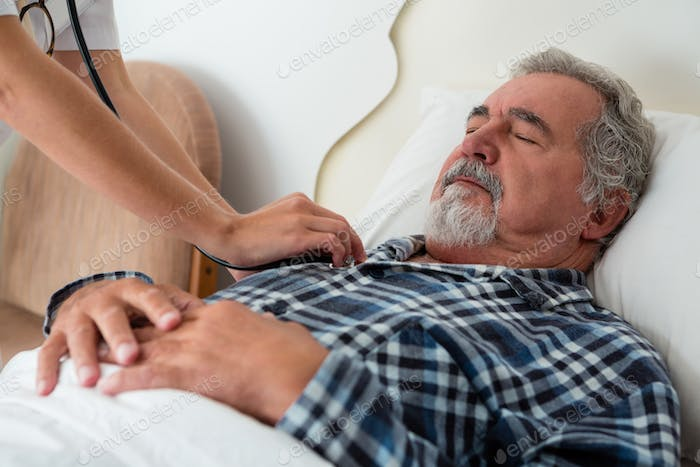 Cropped hands of doctor listening to heartbeats of senior man sleeping on bed