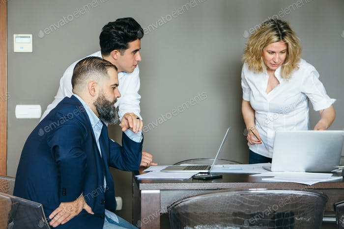 Three colleagues in office room at table